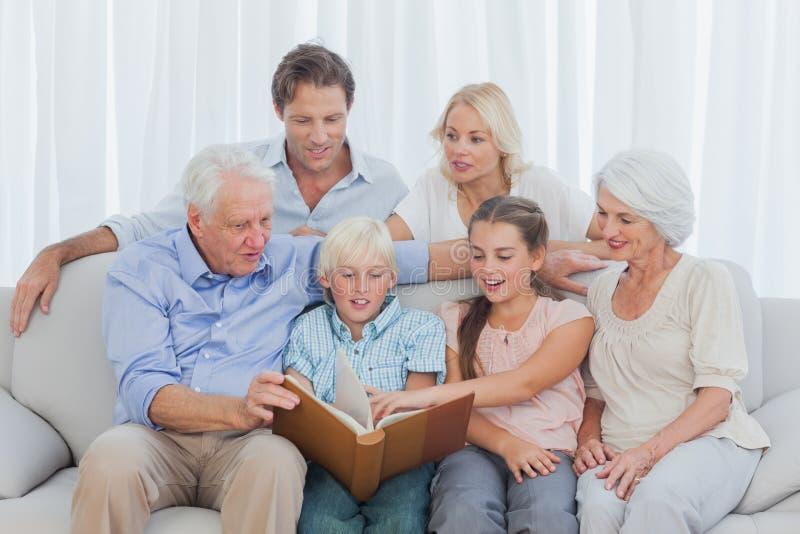 Uitgebreide familie die een fotoalbum bekijken royalty-vrije stock foto's