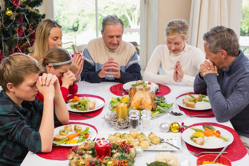 Uitgebreide familie die gunst zeggen vóór Kerstmisdiner royalty-vrije stock foto's