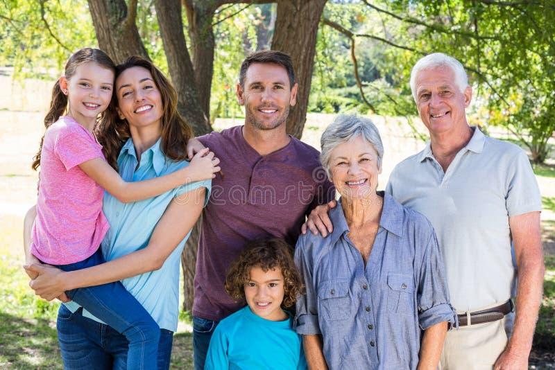 Uitgebreide familie die in het park glimlachen stock afbeelding