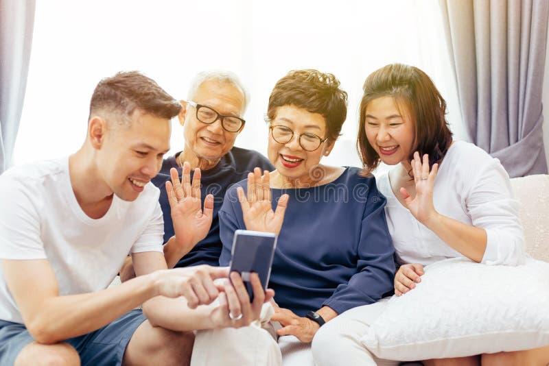 Uitgebreide familie die videotelefoneren en bij de bezoeker golven Aziatische multigeneratiefamilie met hoger en jong paar samen stock fotografie