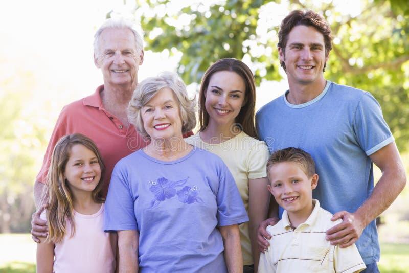 Uitgebreide familie die zich in park het glimlachen bevindt stock afbeeldingen