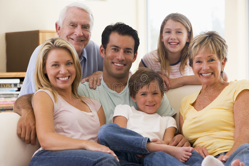 Uitgebreide familie in woonkamer het glimlachen stock foto's