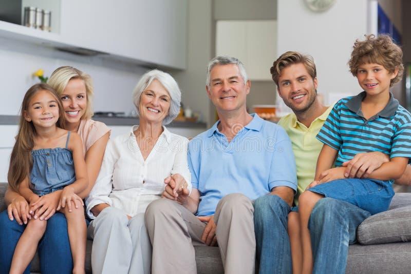 Uitgebreide familiezitting op laag in woonkamer stock foto's