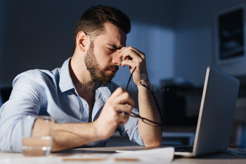 Uitgeput Mens het Werk Overwerk in Donker Bureau royalty-vrije stock afbeeldingen