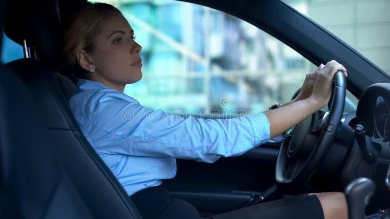 Uitgeput na het werk bedrijfsdamezitting in auto, die over problemen denken stock afbeeldingen