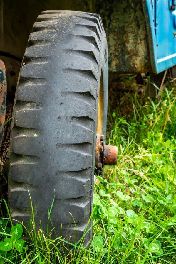 Uitgeputte band van een verlaten auto op weelderig groen gras stock afbeeldingen