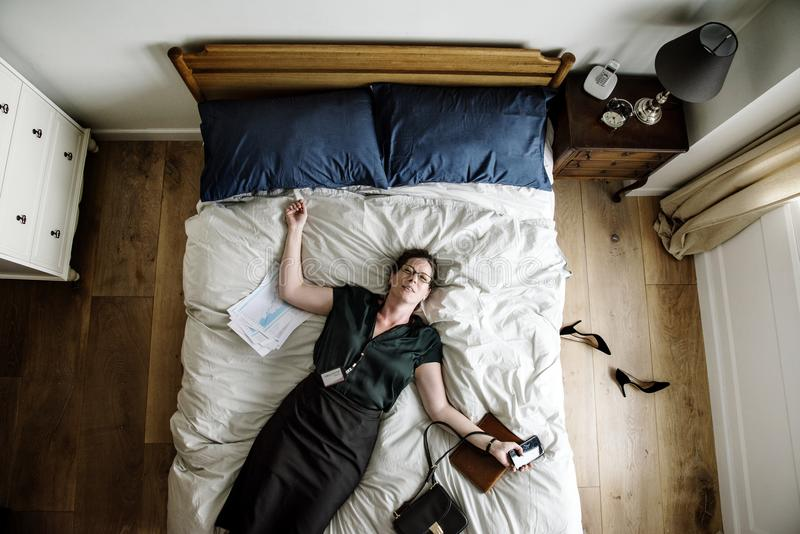 Uitgeputte bedrijfsvrouw die in slaap vallen zodra zij terugkwam royalty-vrije stock foto