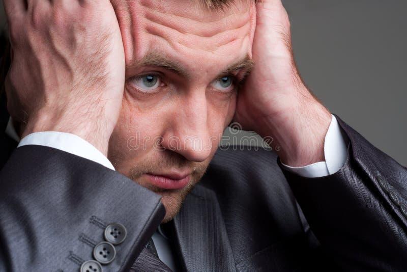 Uitgeputte droevige zakenman die zijn hoofd houdt royalty-vrije stock afbeelding