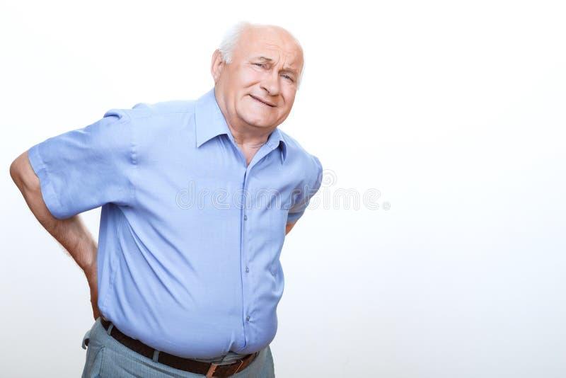 Uitgeputte grootvader wat betreft zijn rug stock fotografie
