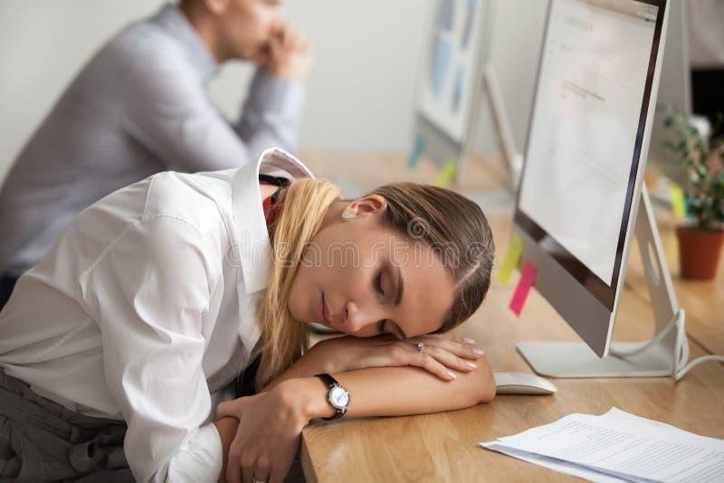 Uitgeputte jonge vrouw die onderbreking nemen aan rust slaap op het werk stock foto