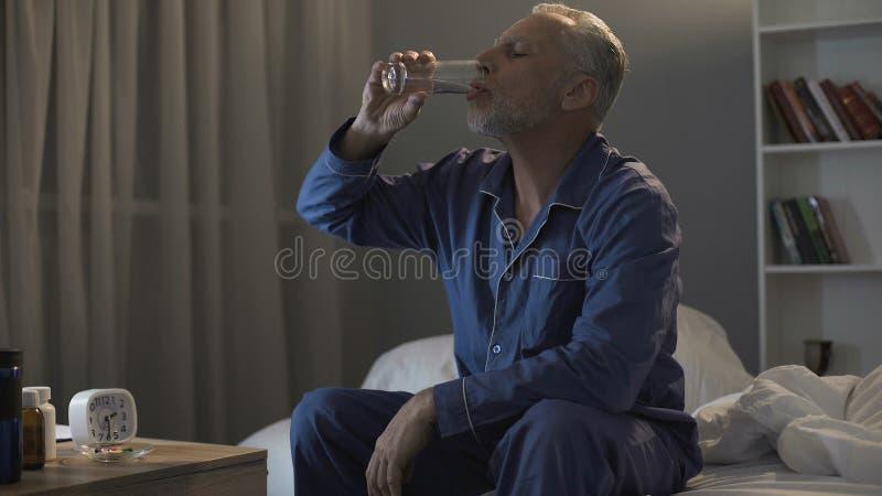 Uitgeputte mens in zijn jaren '50 die in bed zitten en kalmeringsmiddelen nemen bij nacht royalty-vrije stock foto