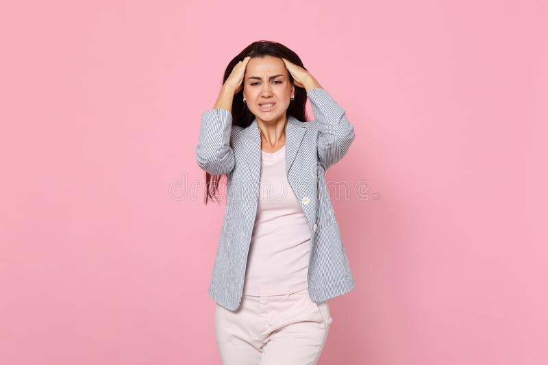 Uitgeputte ontstemde jonge vrouw in gestreept jasje die hoofdpijn hebben, die handen op hoofd zetten op roze pastelkleur wordt ge stock foto's