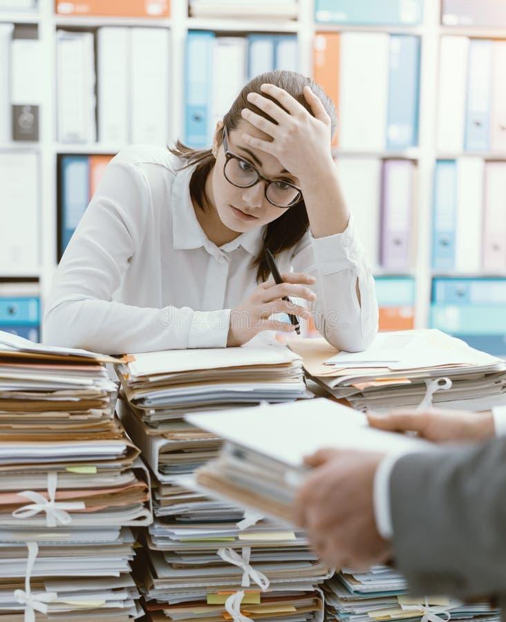 Uitgeputte secretaresse die met het werk wordt overbelast royalty-vrije stock foto's