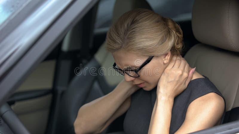 Uitgeputte vrouw die halspijn voelen, die in automobiel, ruggegraatsprobleem, gezondheid zitten royalty-vrije stock afbeelding