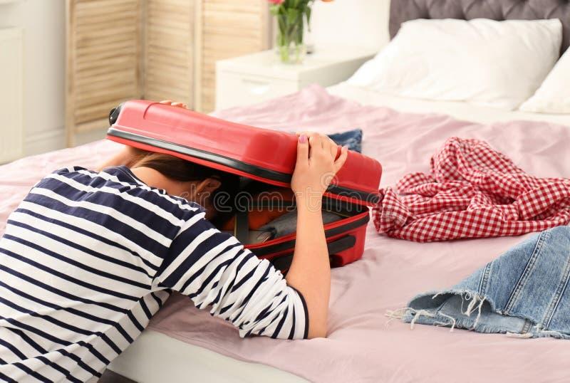 Uitgeputte vrouw met haar hoofd binnen van koffer royalty-vrije stock foto