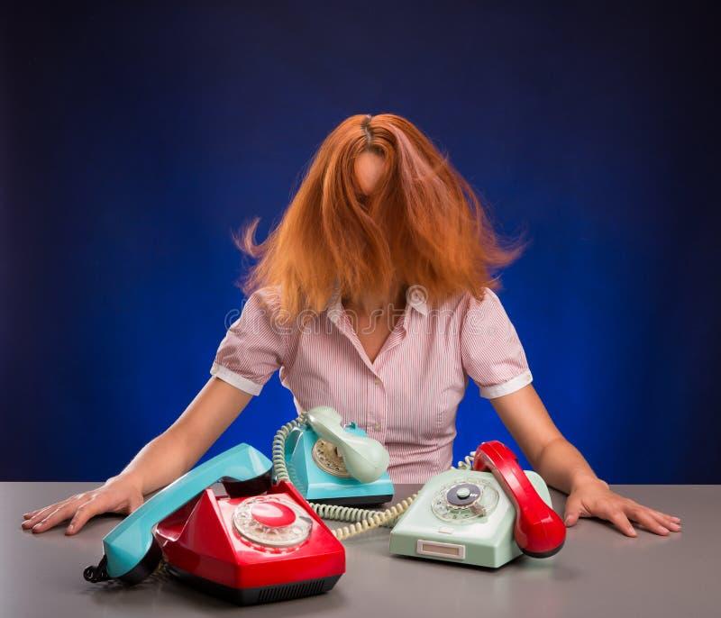 Uitgeputte vrouw met kleurrijke telefoons stock afbeelding