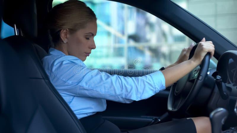 Uitgeputte vrouwen sluitende ogen die in auto zitten, die na het harde werkdag proberen te ontspannen stock foto