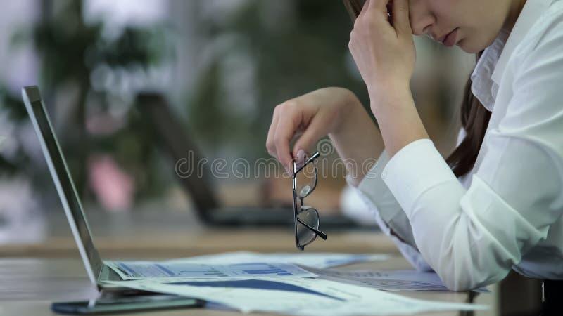 Uitgeputte vrouwenmanager die glazen opstijgen en ogen, overwerkte werknemer wrijven royalty-vrije stock fotografie