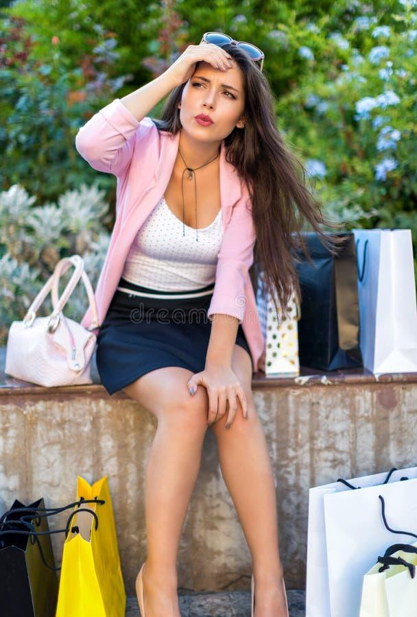Uitgeputte winkelende vrouw met vele het winkelen zakken rond haar stock foto