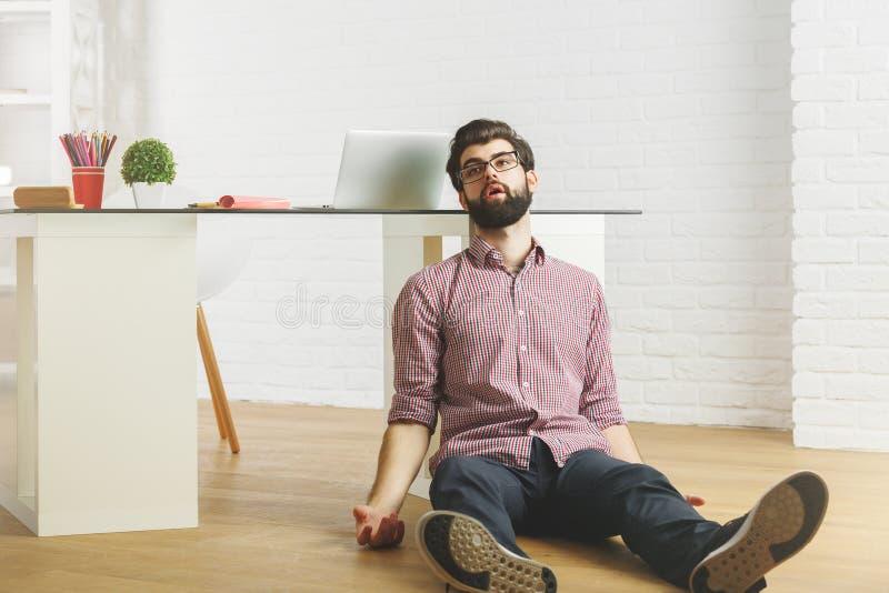 Uitgeputte zakenman op bureauvloer stock afbeeldingen