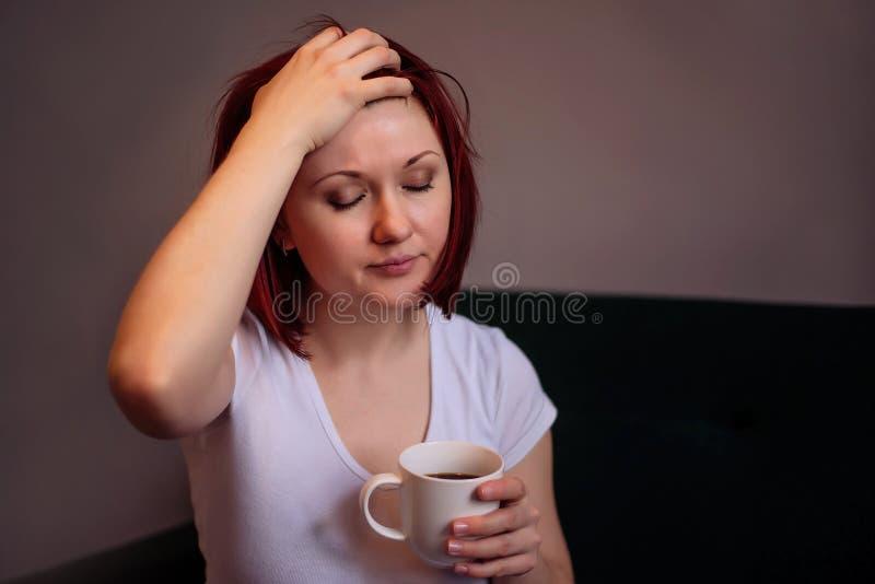 Uitgeputte of zieke vrouwenzitting op bank met kop van de hand van de koffieholding op voorhoofd Een klein onderbrekingsconcept royalty-vrije stock foto