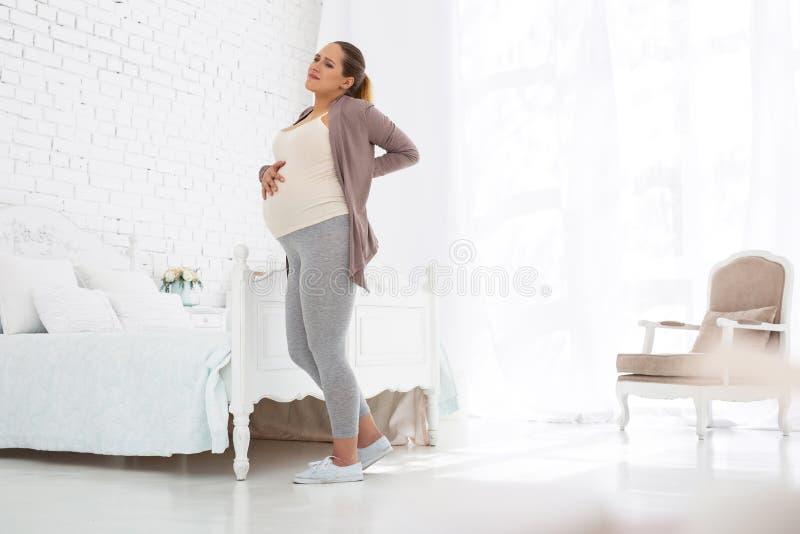 Uitgeputte zwangere vrouw die aan rugpijn lijden stock afbeeldingen