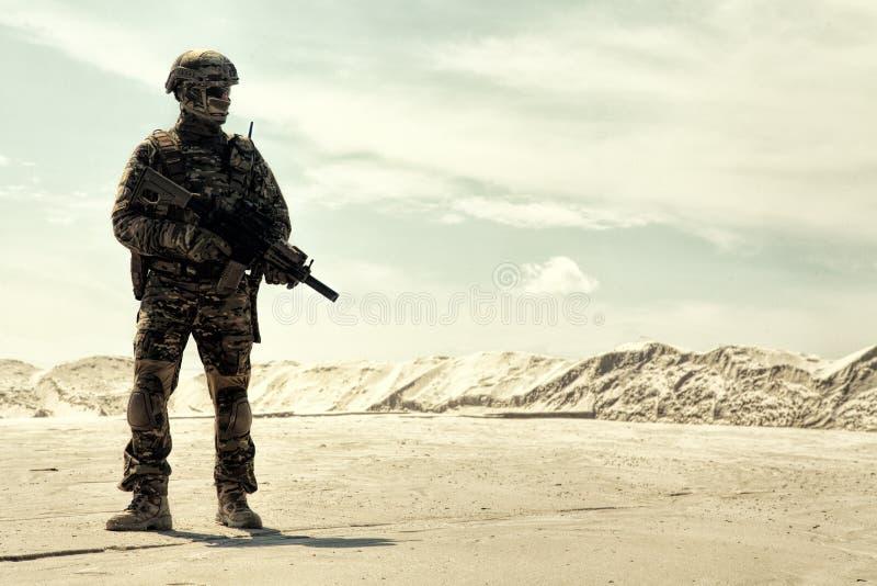 Uitgeruste legermilitair met geweergangen in woestijn stock fotografie