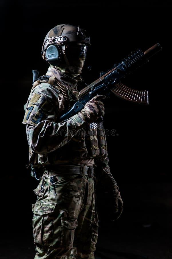 Uitgeruste militair die zich in profiel bevinden en automatische machine opgeheven houden omhoog stock fotografie