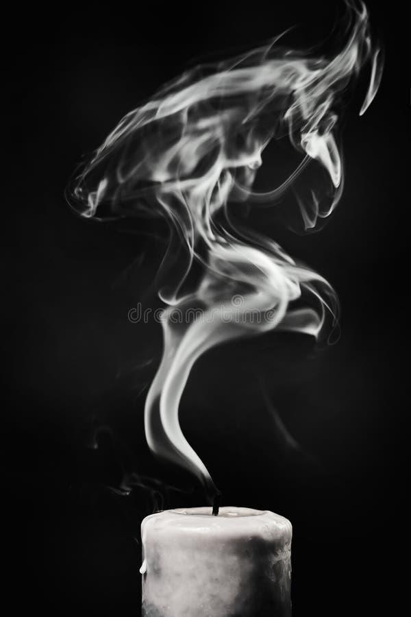 Uitgestorven witte kaars met rook op een zwarte achtergrond stock foto