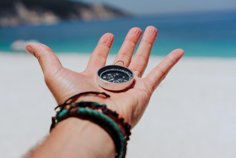 Uitgestrekte hand die zwart metaalkompas houden tegen wit zandig strand en blauwe overzees Vind uw manier of doelconcept stock fotografie