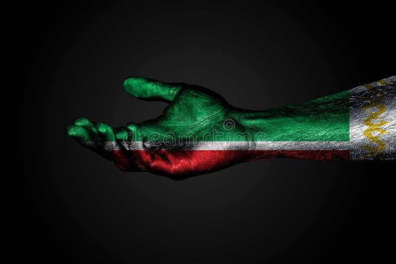 Uitgestrekte hand met een getrokken vlag van Tchetchenië, een teken van hulp of een verzoek, op een donkere achtergrond stock foto's