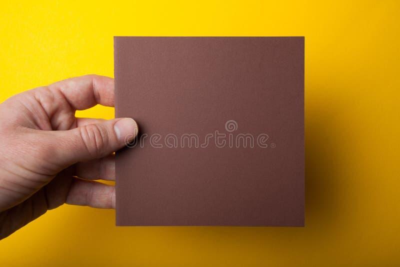 Uitnodigingsprototype, vierkante Vlieger in mannelijke handen, die een pakpapierspatie op een gele achtergrond houden royalty-vrije stock afbeelding