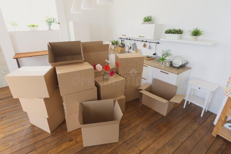 Uitpakkende dozen in nieuw huis en het wegzetten van dingen in keuken, grote kartondozen in nieuw huis Het bewegen zich aan een n stock afbeeldingen