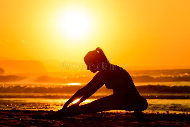 Uitrekkende oefeningen op strand bij zonsondergang royalty-vrije stock foto