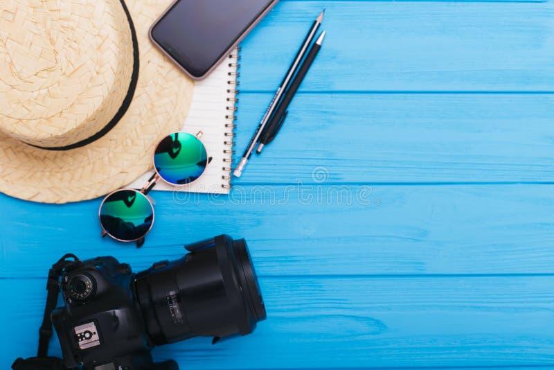 Uitrusting en toebehoren van reiziger op blauwe achtergrond met exemplaarruimte reis concept Vlak leg stock afbeelding