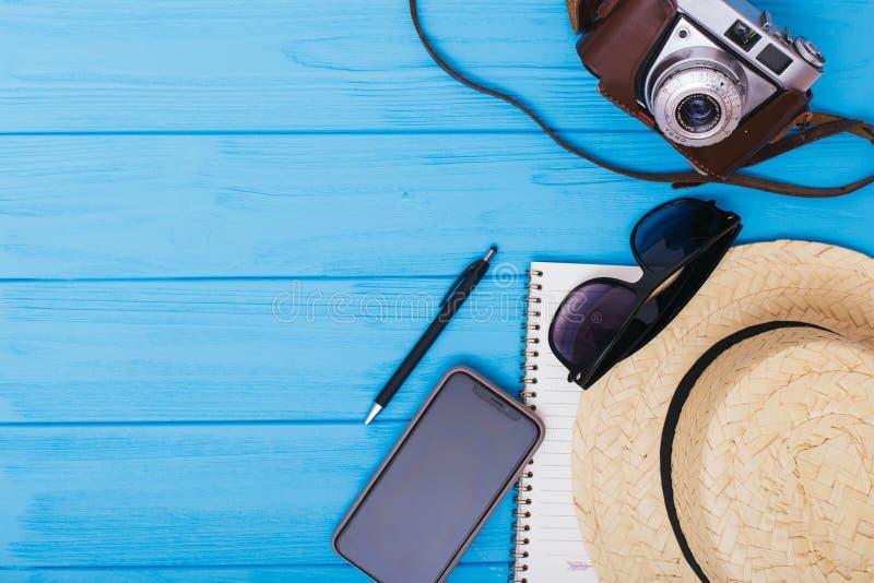 Uitrusting en toebehoren van reiziger op blauwe achtergrond met exemplaarruimte reis concept Vlak leg stock foto