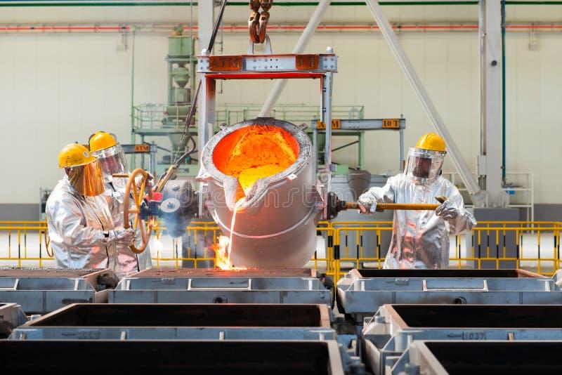 Uitsmelting in een metallurgische installatie Gesmolten metaalmorserij stock afbeeldingen
