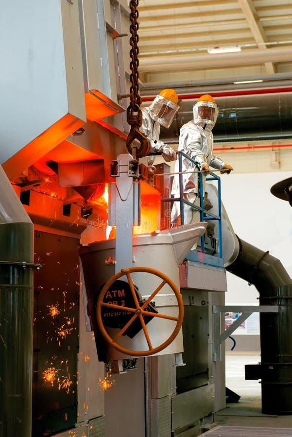 Uitsmelting in een metallurgische installatie Gesmolten metaalmorserij stock foto