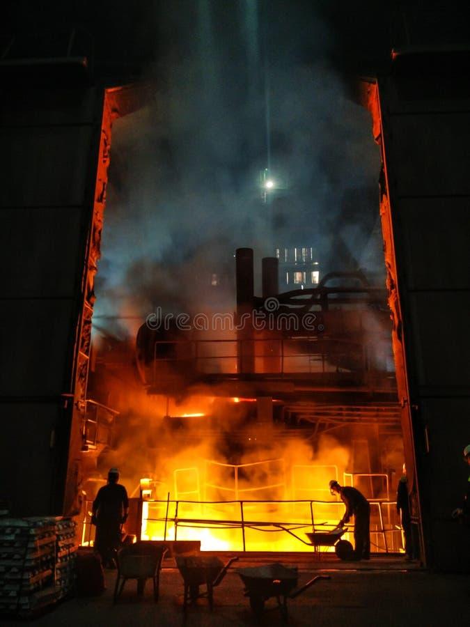 Uitsmelting van metaal in grote gieterij Ijzer en staalproductie bij een metallurgische installatie Staalarbeider Metallurgieproc royalty-vrije stock fotografie