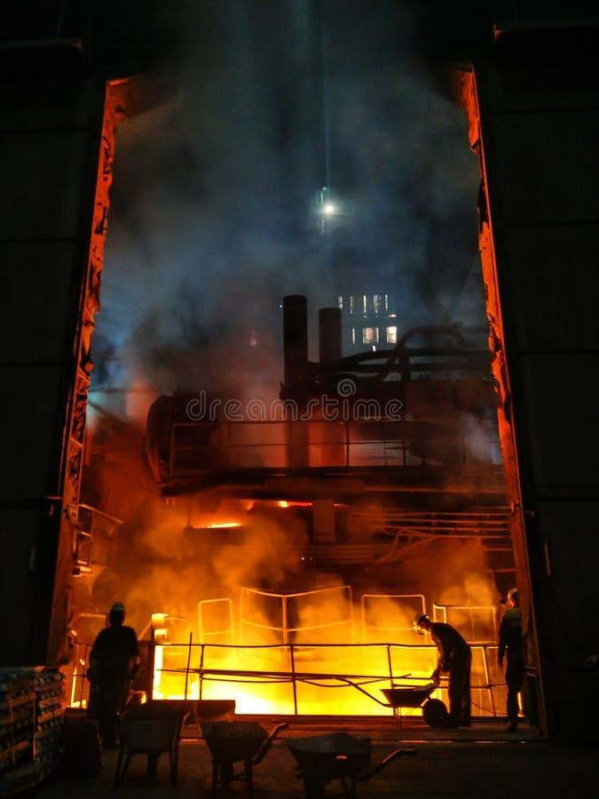 Uitsmelting van metaal in grote gieterij Ijzer en staalproductie bij een metallurgische installatie Staalarbeider Metallurgieproc stock foto's