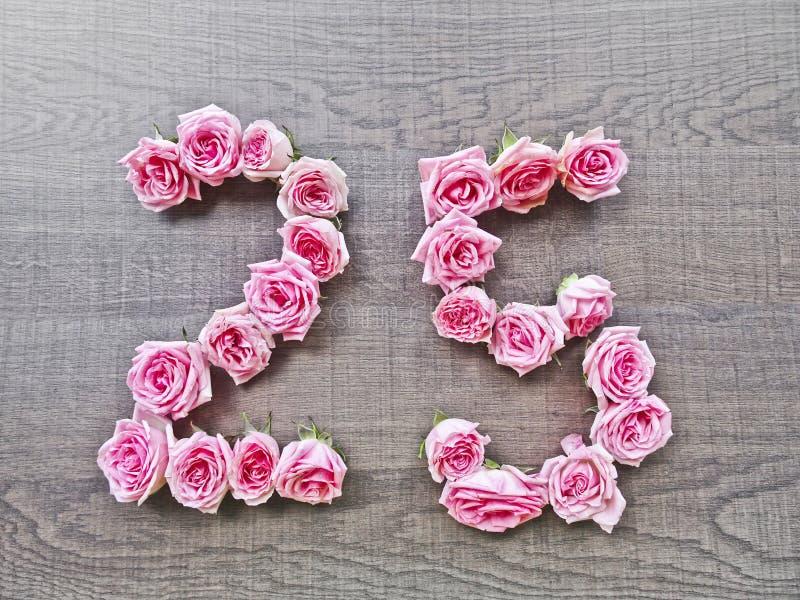 25 - uitstekend aantal roze rozen op de achtergrond van donker hout stock foto's