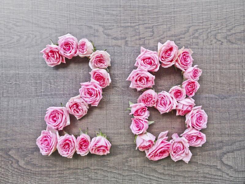 28 - uitstekend aantal roze rozen op de achtergrond van donker hout stock afbeelding
