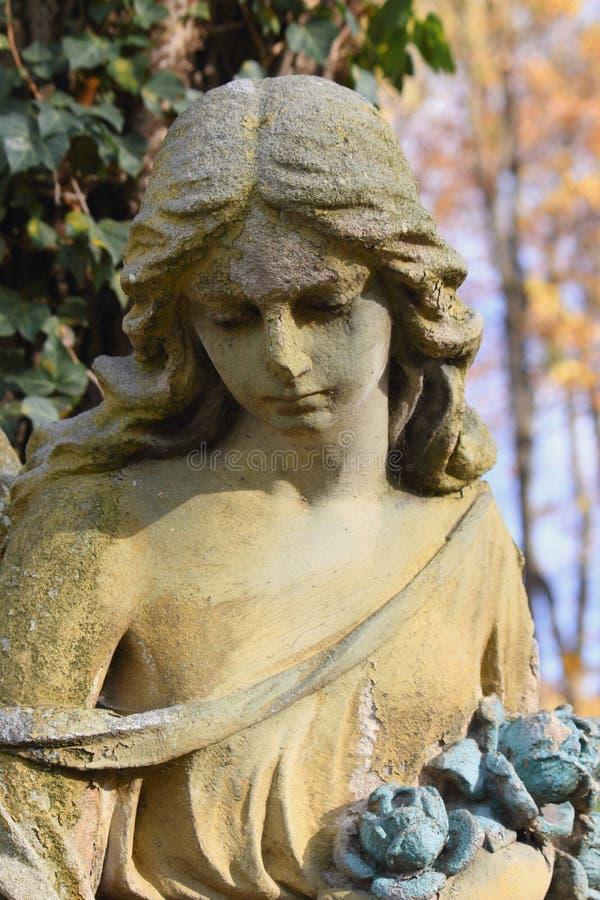 Uitstekend beeld van een droevige engel op een begraafplaats (fragment) stock foto
