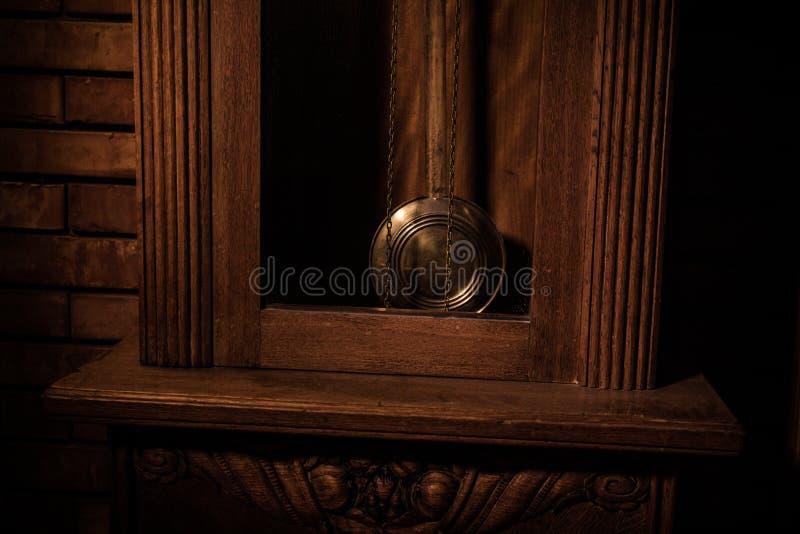 Uitstekend binnenland in westelijke stijl Grote houten antieke klok met slinger stock afbeeldingen