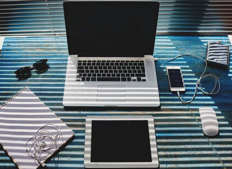 In uitstekend blauw is de houten lijst een PC-computer, een tablet en een notitieboekje voor verslagen stock afbeelding