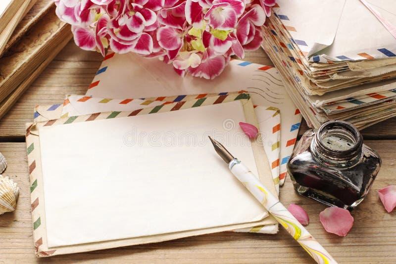 Uitstekend brieven, boeken en boeket van roze hortensiabloemen stock foto's