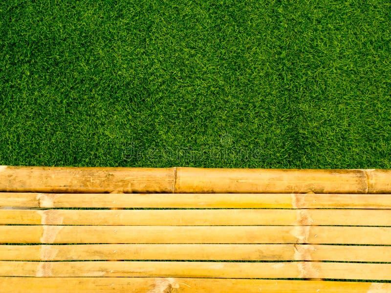 Uitstekend bruin en geel bamboe met verse groene grasachtergrond royalty-vrije stock foto