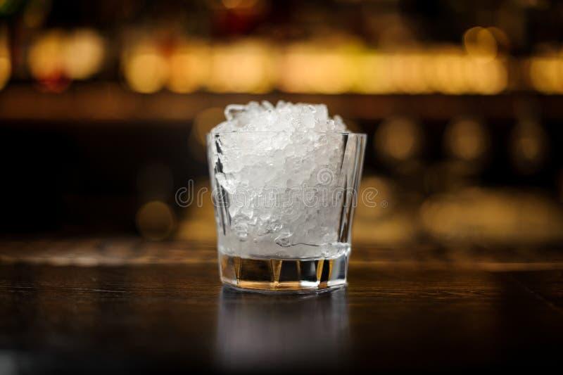 Uitstekend cocktailglas van verpletterd ijs die zich op de lege bartribune bevinden stock foto's