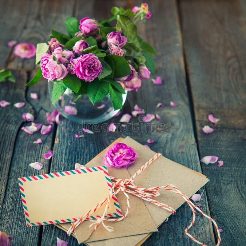 Uitstekend concept - boeket van verwelkende theerozen in vaas, stapel van oude brieven in enveloppen en lege groetkaart op oude h royalty-vrije stock foto