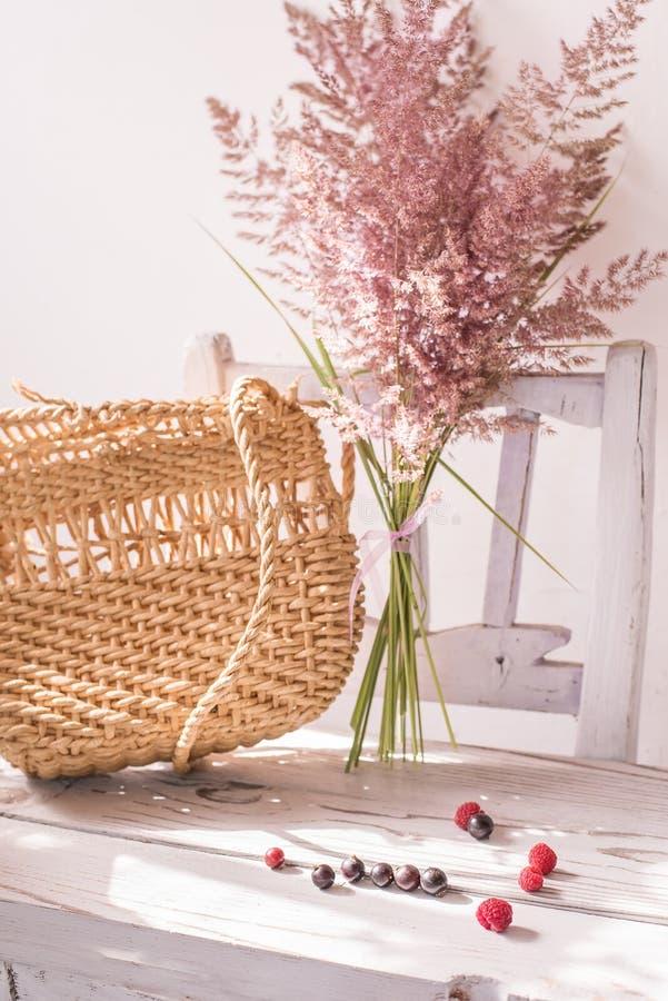 Uitstekend de zomerstilleven Een gelopen zak en droge oren van gras op een oude witte stoel eenvoudige uitstekende punten royalty-vrije stock afbeeldingen